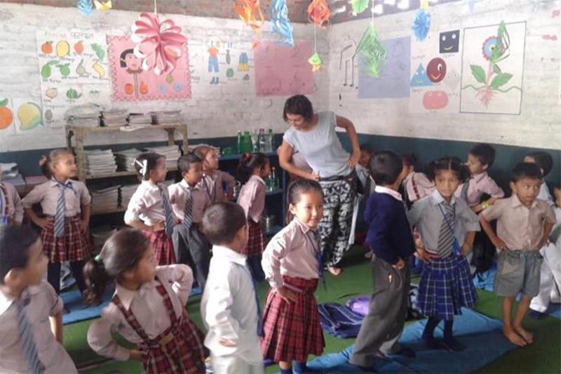 Una voluntaria bailando con los niños en una escuela de primaria